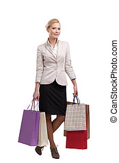 Attractive attractive business woman in a light beige suit holding shopping bags, isolated on white background