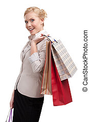 Attractive blonde businesswoman in a light beige suit holding shopping bags, isolated on white background