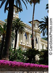 San Remo casino white facade with palms and flowers,...