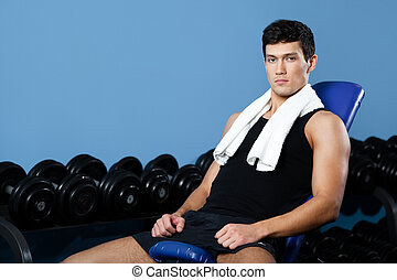 Athletic man rests in gym class - Athletic man rests sitting...