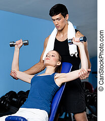 Trainer helps woman to exercise with weights