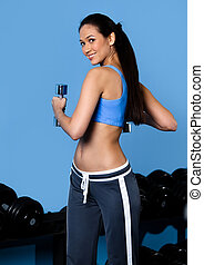Athlete woman works out with dumbbells