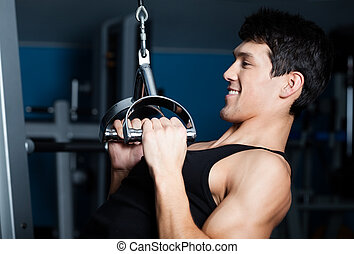 Athletic man works out on training apparatus - Athletic...