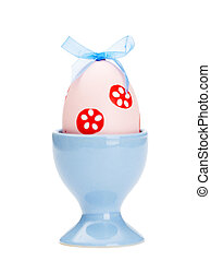 Pink easter egg is in blue egg cup