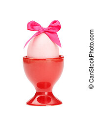 Easter egg with pink bow in red egg cup