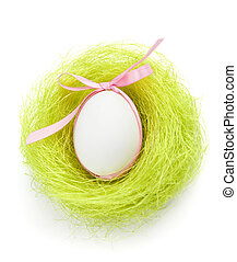 Egg with bow is in the nest of green sisal fibre - Egg with...