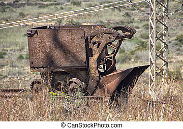 rusted old machines to collect coal from the tracks