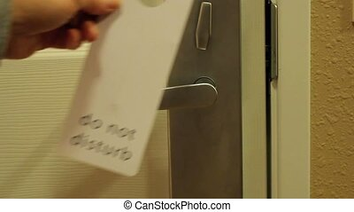 do not disturb - hand placing a do not disturb sign on a...