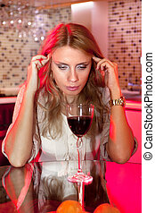 sad woman in kitchen with glass of wine