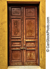 Antique wooden door on yellow cement wall
