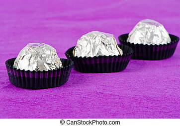 andy - Three tasty chocolate candy on a purple background