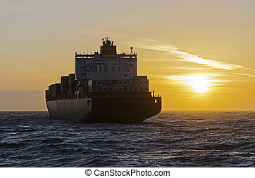 Container ship heading towards sunset on the north sea in...