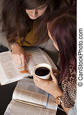 Bible Study And Coffee - Two young women study the bible...