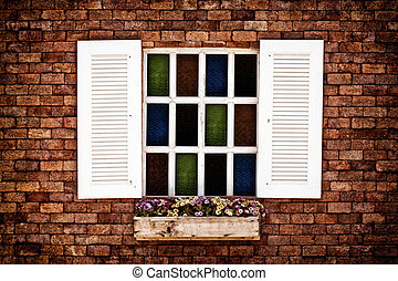 White window colorful glass on brick wall of vintage house...