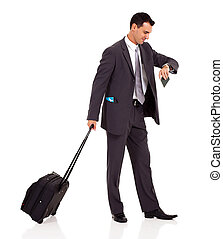 businessman walking with trolley bag and looking at his...