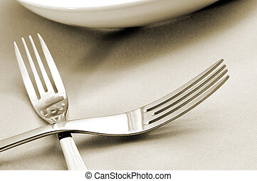 forks and plates on a tablecloth - closeup of a couple of...