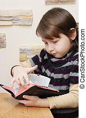 Holy Bible - The little girl reads the Holy Bible