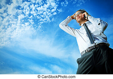 calling man - Successful business man standing over blue sky...