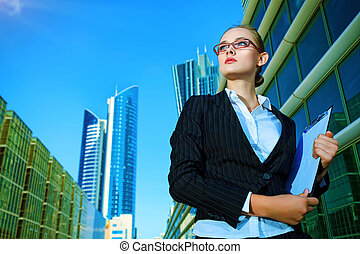 looking away - Young business woman standing in the big city...
