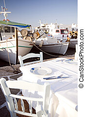taverna setting in harbor with fishing boats - greek island...