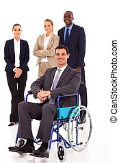 businessman in wheelchair with colleagues in background