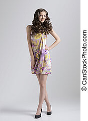 wavy brunette with colored dress in full-lenght