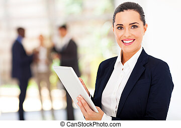 beautiful female corporate worker with tablet computer in...
