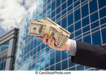 Male Hand Holding Stack of Cash with Corporate Building...
