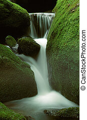 A small mountain stream waterfall through bright green moss covered rocks
