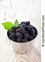Small bucket of fresh blackberries on old wooden table -...