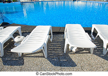 swimming pool surrounded by chairs