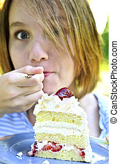 Girl eating a cake - Teenage girl eating a piece of...