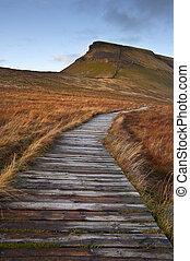 Wooden footpath over bog land leading ot Pen-y-Ghent in Yorkshire Dales National Park