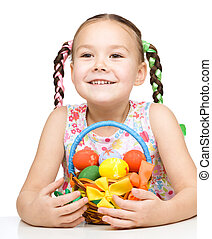 Little girl with basket full of colorful eggs preparing for...