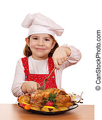 little girl cook cutting roast chicken