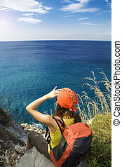 hiking - young woman sitting on top of a cliff and looking...