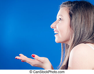Young happy woman catching empty space over bluescreen