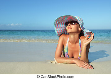Beautiful young woman lying on the Roatan beach dreaming