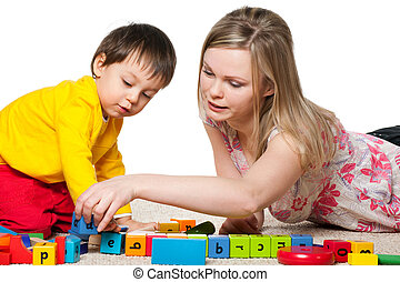 Mother and son are playing on the carpet with blocks