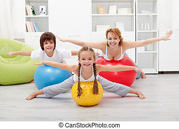 Happy kids exercising with their mother using large rubber...