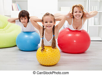 Gymnastic at home - with large balls - Kids and woman doing...