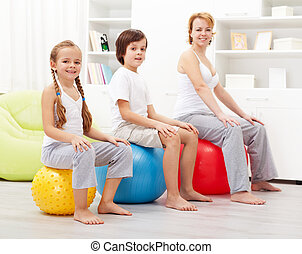 Kids exercising with their mother using large gymnastic...