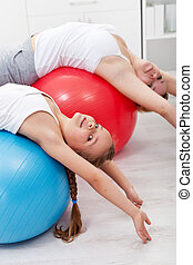 Stretching gymnastic exercise - woman with little girl using...