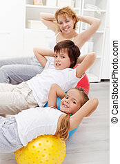 Kids with their mother doing gymnastic exercises with large...