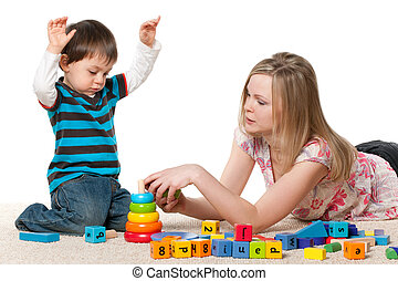 Playing on the carpet with blocks - Young mother and a...