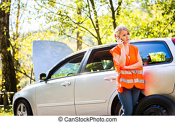 Young female driver wearing a high visibility vest, calling...