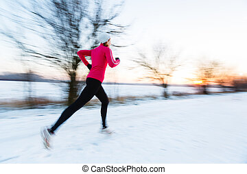 Young woman running outdoors on a cold winter day (motion...