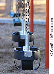 Swing Set - View of toddler swings in the foreground and...
