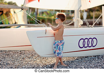 boy and boats - boy on the beach in shorts and sunglasses...
