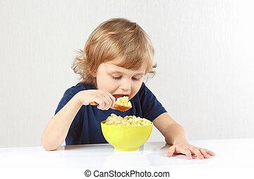 Beautiful blonde child eating a millet porridge